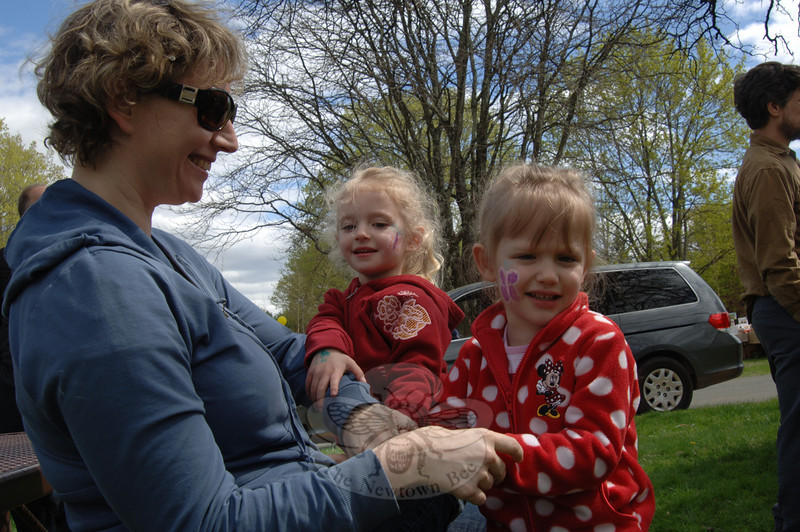 Anne Bloss sits with her daughters Julia, left, and Katie after the girls had butterflies painted on their cheeks during the Earth Day Festival.
