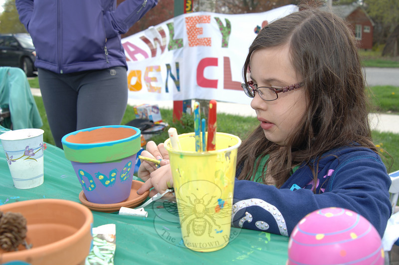 Alex Quinby takes her time to hand paint a flower pot in purple, green, yellow, and blue.  (Bobowick photo)
