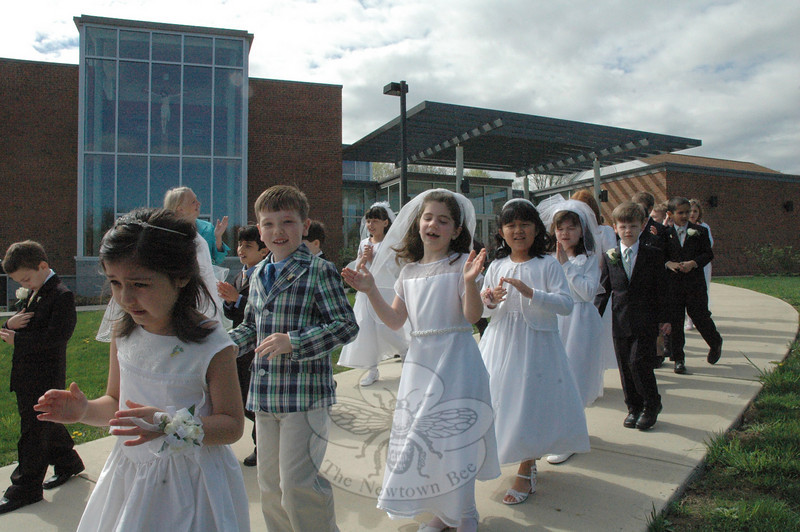 Some young St Rose of Lima Church parishioners walk from St Rose School, in the background, to St Rose Church on the morning of Saturday, April 30, to receive their first communion at Mass. Several dozen new communicants participated in the Mass that morning, which was followed by an afternoon first communion Mass. Also, two first communion Masses are scheduled for Saturday, May 7, and one first communion Mass for Sunday, May 15. Overall, about 200 children will receive their first communion at the church at the five Masses.  (Gorosko photo)