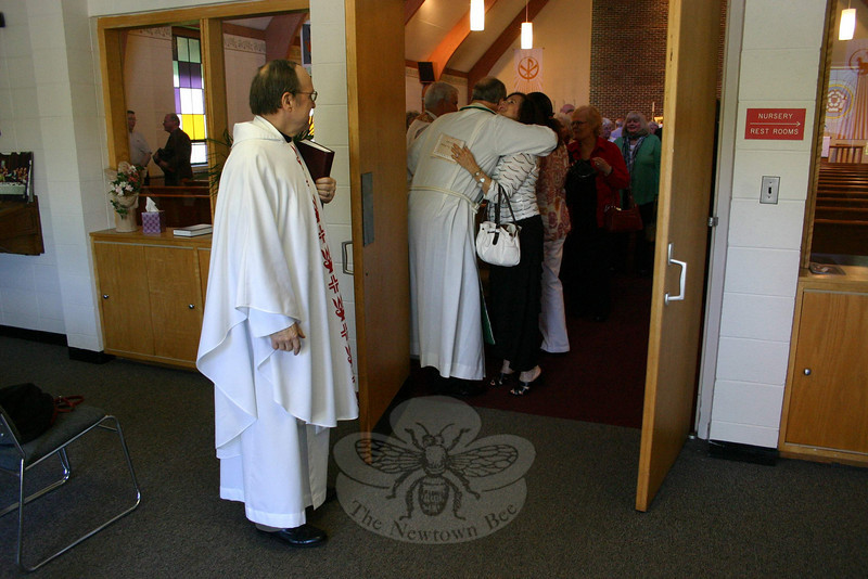 Pastor Greg Wismar, on the left, waits for parishioners of Christ the King to emerge from the sanctuary following worship services on May 1. In the doorway, Sandi Schipul was hugging the Reverend James Ilten, who was the church's founding pastor. Mrs Schipul is married to the Reverend Robert Schipul, who was also a guest last weekend on Homecoming Sunday.  (Hicks photo)