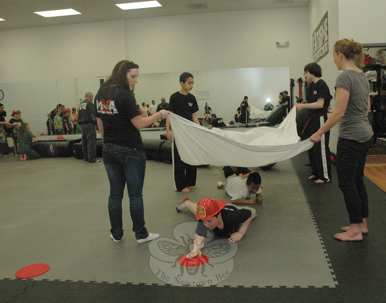 Children at Extreme Fitness Martial Arts conduct a drill on the safety techniques they would use to flee from within a burning building.  (Gorosko photo)