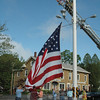 Members of the Newtown Lions Club, Newtown Hook & Ladder firefighters, and David Lydem, who is known as the Keeper of the Flagpole, prepared to raise the large flag that flies on the Main Street flagpole during the summer and fall. The flag measures 20 feet by 30 feet. (Gorosko photo)