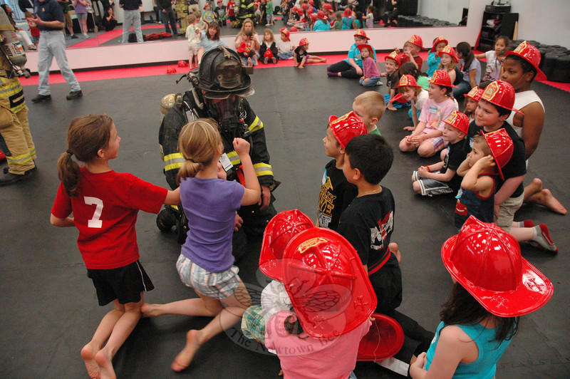 A group of children at Extreme Fitness Martial Arts at Plaza South at 266 South Main Street get a close look at a firefighter dressed in full firefighting gear during a public safety day program at the martial arts center on May 21.  (Gorosko photo)