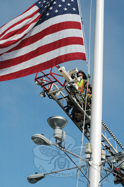 Members of Newtown Hook & Ladder stationed on the volunteer fire company's aerial ladder carefully removed the small flag from the Main Street flagpole on May 21, in preparing to hoist the large flag that flies on the pole in the summer and fall. The small flag measures 12 feet by 18 feet. The small flag is being presented to the family of the late Navy Seal Jason D. Lewis, a native of Brookfield, who was killed in Baghdad during a combat mission on July 6, 2007.  (Gorosko photo)