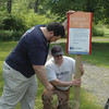 Newtown residents and corporate neighbors pitched in lending muscle and some creative flair to three United Way Day of Caring projects June 8. Co-workers Jeff Gustaitis and Evan Horowitz represented Boehringer Ingelheim whose volunteers installed the company's fourth Born Learning Trail at Dickinson Park, installing one of the trail markers.  (Voket photo)