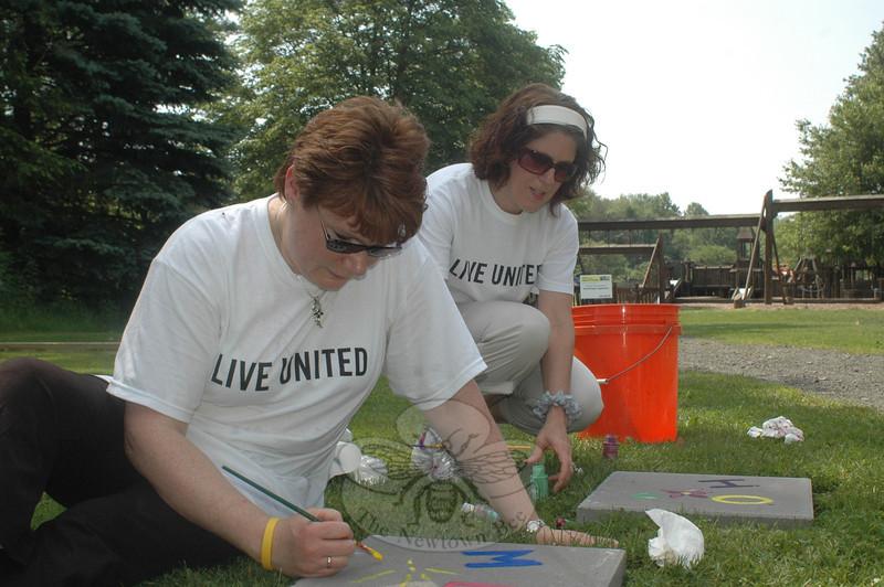 Newtown residents and corporate neighbors pitched in lending muscle and some creative flair to three United Way Day of Caring projects June 8. Peggy Henckel, in foreground, and Mary Arther represented Boehringer Ingelheim whose volunteers installed the company's fourth Born Learning Trail at Dickinson Park.  (Voket photo)