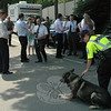 Police K-9 Officer Felicia Figol, right foreground, tends to German shepherd Baro on a hot June 8 as a group of visitors from the Polish national police agency toured the police station at 3 Main Street. The visitors checked the police department's specialty units, including its traffic enforcement squad, mobile command post, and K-9 unit. Police demonstrated the dog's law enforcement skills at The Pleasance, which is next door to the police station.  (Gorosko photo)
