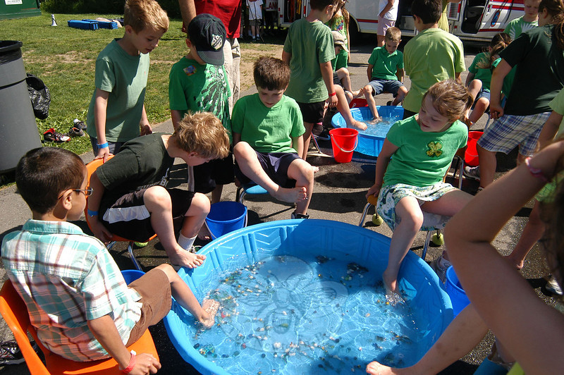 Hawley student Matthew Pereira, pictured, was one of many students who climbed their way through a blown-up obstacle course Thursday, June 2, during the school's annual year-end field day event. Hawley School students had myriad challenges during their annual field day on June 2, including picking pebbles out of a water-filled tub with toes (pictured), working as a class to lift a parachute, filling buckets with water-soaked sponges, and inside the school Survivor-like challenges were held along with a game of Bingo.  (Hallabeck photo)