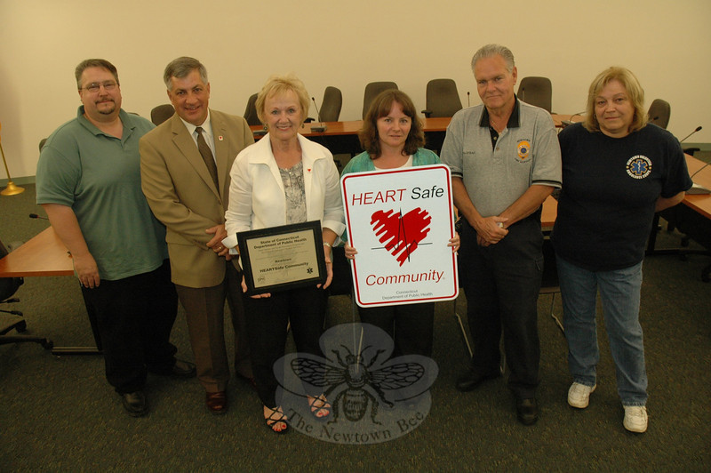 The state has designated Newtown as a HEART Safe community, recognizing the town's efforts in the area of cardiac care. In ceremonies at Newtown Municipal Center on June 17, Gary St Amand, second from left, a health program associate with the heart disease and stroke prevention unit of the state Department of Public Health, presented a plaque and road sign to the town signifying its HEART Safe status. Among those involved in the HEART Safe program in Newtown are, from left, John Voket of The Newtown Bee; First Selectman Pat Llodra; Health Director Donna Culbert; Emergency Management Director Bill Halstead; and Liz Cain of Newtown Volunteer Ambulance Corps.  (Gorosko photo)
