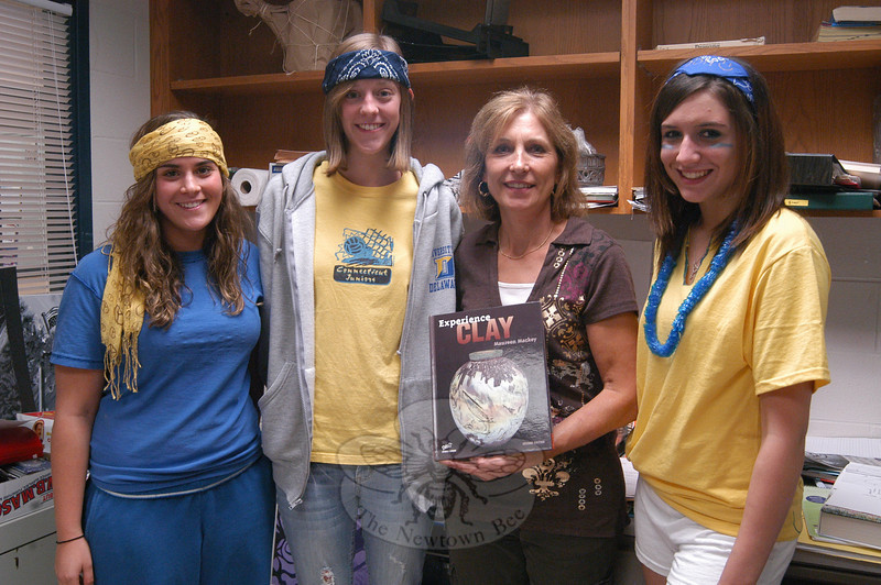 Newtown High School art teacher Carol Pelligra holds the newly published book Experience Clay by Maureen Mackey, which includes images of ceramic work created by seniors, from left, Nicole Gindraux, Emily Rowe, and Taylor Johnson.  (Hallabeck photo)
