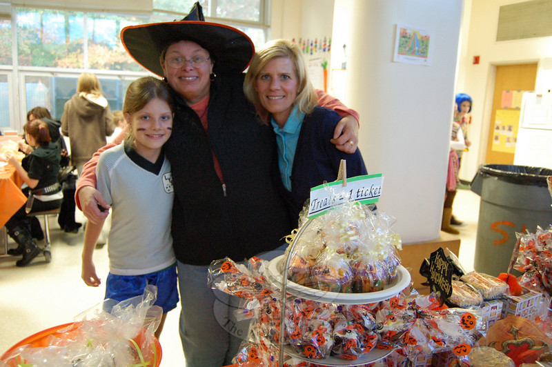 From left, Rachel Wolf, Kathy Gramolini, and Chris Wolf oversaw a table of treats during the Sandy Hook School Family Fair on Friday, October 22. Students walked the school's hallways in Halloween outfits. The night included a Haunted House, created by Sue and Dean Harrell of Picture Perfect Landscaping.  (Hallabeck photo)