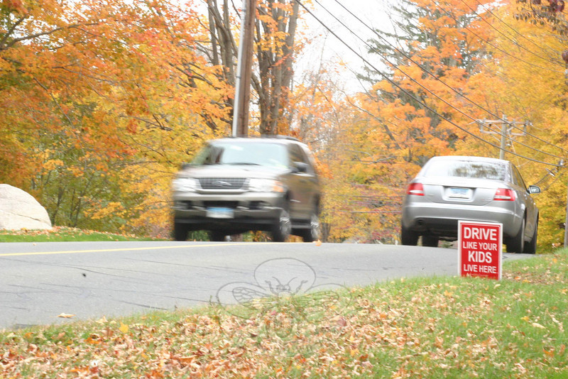 "Neighbors along one section of Boggs Hill Road recently began posting red and white signs along the roadway imploring drivers to ""Drive Like Your Kids Live Here."" One of the residents, Amanda Carlin, said she and her neighbors have been working with the police department to get drivers to reduce their speed in their neighborhood, and they are hoping the signs will offer an additional incentive to just slow down. Apparently one passerby either did not like the message or liked it so much they wanted to share the idea in their own neighborhood. Ms Carlin told The Bee she has already had to replace one of her signs after it was stolen.  (Hicks photo)"