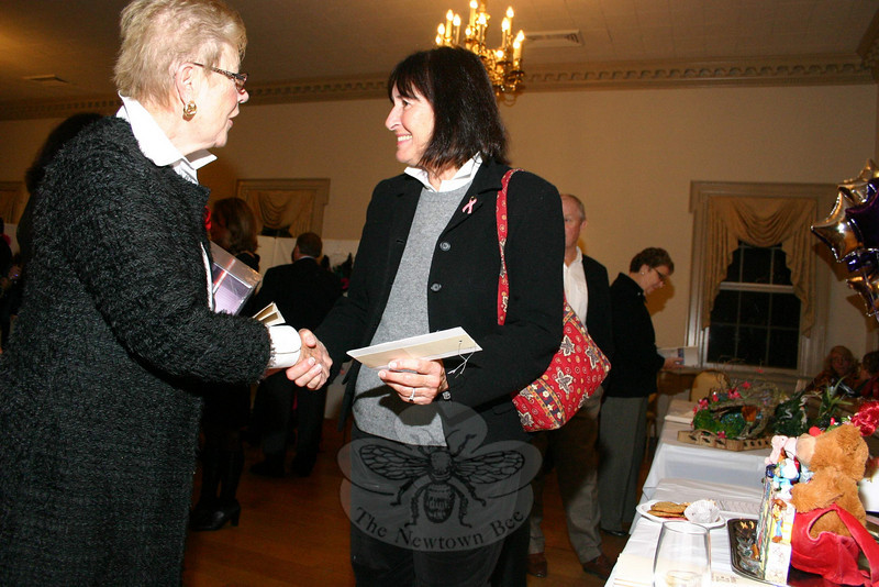 "Joy Previdi, the executive director of Ann's Place (left), and Shane Miller were both eyeing the same work, ""Toy Chest"" by Hunter Ross, before coming to a mutual agreement on the bra's new home.  (Hicks photo)"