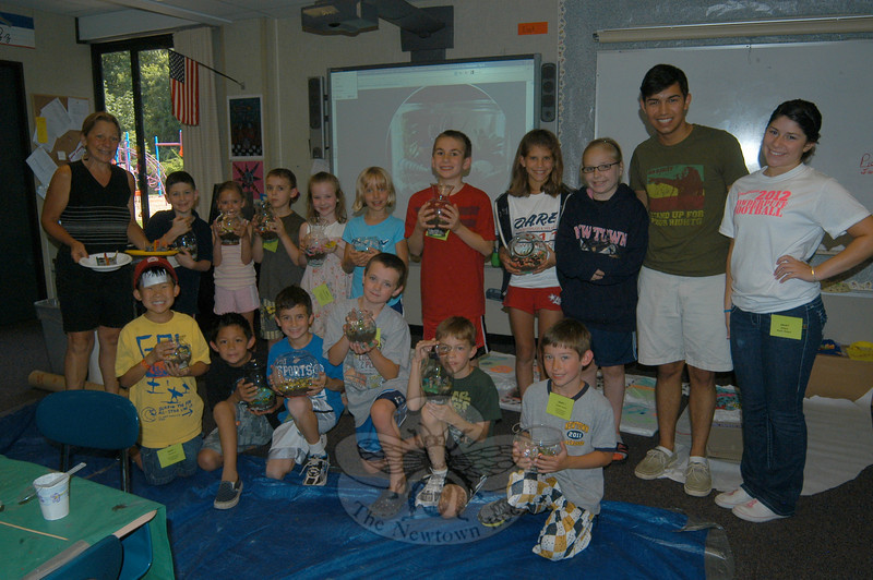 Students in the first session of SMART (Summer Music and Arts) Summer Camp Small World Design program hold terrariums they created and stand with course instructor Marianne Mulvaney, left, and SMART interns Troy Neves, second from right, and Katie Peters, right.  (Hallabeck photo)