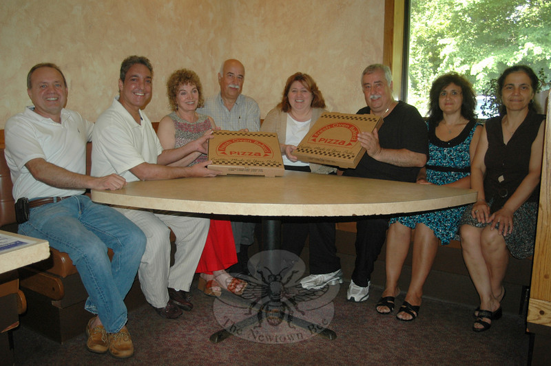 The new and former owners of Newtown Pizza Palace have known each other for years through family ties and friendships, and have worked together for months as the popular local eatery has transitioned from the Antonopoulos to the Dushku and Sofronas families. Seated at the restaurant, from left, are Gino Dushku, Elias and Catherine Sofronas, John Antonopoulos, Dila Dushku, Jimmy, Effie, and Vassi Antonopoulos. Brother Alex Dushku is not pictured.  (Voket photo)