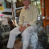 R. Scudder Smith perches on the ball of tinfoil that has served to measure his years at The Newtown Bee. He is still having too much fun at the paper, he says, to retire — the original intention, once the sphere of sandwich wrappers preserved through the years no longer fit through his office doorway.  (Crevier photo)