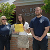 Animal Control Officer Carolee Mason, left, received a $350 check from eighth grade St Rose student Larissa Spies, who has worked for the second year in a row to benefit Newtown's animals. Assistant Animal Control Officer Matt Schaub also greeted Larissa in early June to receive the funds she raised through Kids For Canines, a volunteer organization aimed at benefiting the Newtown dog pound.  (Bobowick photo)