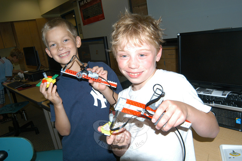 Thomas Armstrong, left, and Hunter Smith hold Lego robots they created in the summer WeDo Robotics course.  (Hallabeck photo)