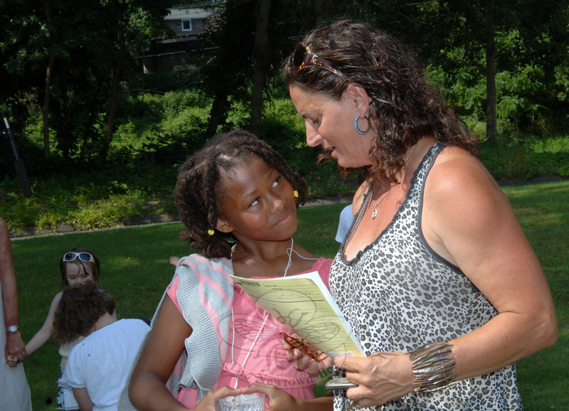 Mary Sireci of Newtown, right, welcomes Aza Monday afternoon as she and a group of other children arrived at Christ The King Lutheran Church, where they met host families from surrounding towns. The Fresh Air Fund made summer vacations possible for the inner-city children.  (Bobowick photo)
