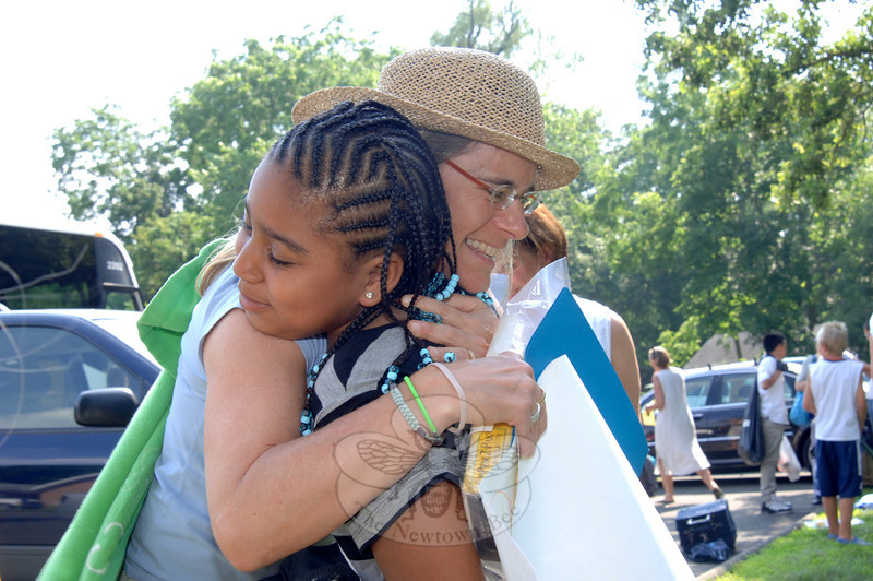 Kendall Webb of Weston hugs Kayla, and welcomes her back for another summer visit through the Fresh Air Fund's summer vacation program.  (Bobowick photo)