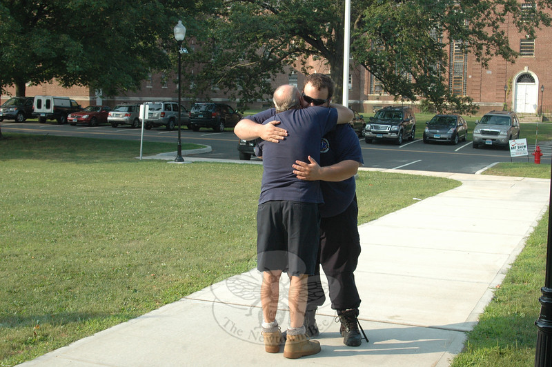 This week, Bill Ross, in foreground, hugged Paramedic Chris Neary in appreciation of his response late last week to his call for emergency help. Mr Neary was among the first life-saving emergency responders on the scene minutes after yellowjackets, disturbed by a lawn mower, swarmed and stung Mr Ross more than 28 times, sending him into near fatal anaphylactic shock.  (Voket photo)