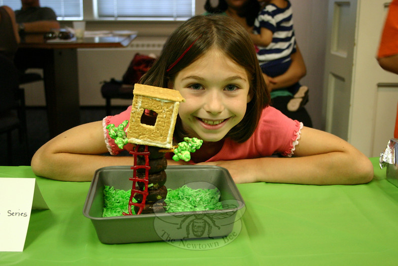 """Rosie Simms smiles proudly with the entry her family created for C.H. Booth Library's Edible Book Contest. The family created the magical portal in Frog Creek, Penn., that is the focus of Mary Pope Osborne's Magic Tree House series.  (Hicks photo)<br /> <br /> PLEASE NOTE a full gallery of photos from this event, with images of every entry (these are the photos that made up the slide show that accompanied the story about the Edible Book Contest), can be viewed here: <br />  <a href=""""http://photos.newtownbee.com/Events/2011-Edible-Books-Contest-at/18154663_43dzvp#1394153855_9F2VNch"""">http://photos.newtownbee.com/Events/2011-Edible-Books-Contest-at/18154663_43dzvp#1394153855_9F2VNch</a>"""