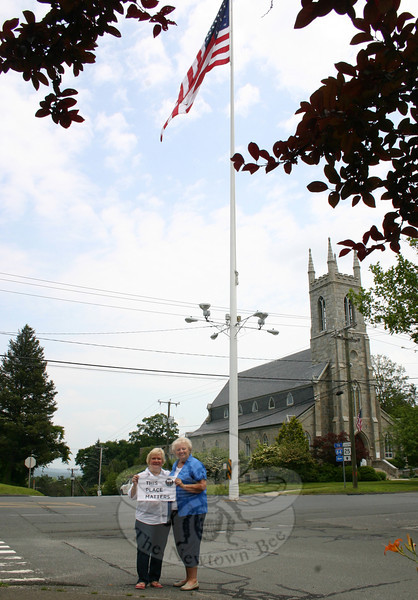 "After 135 years, it is pretty hard to imagine the intersection of Main Street at Church Hill Road and West Street without the 100-foot steel flagpole the currently makes its home in the middle of that major roadway.  Newtown Woman's Club, GFWC, Inc is continuing its ""This Place Matters"" series with a look this month at the flagpole, a historic landmark that has been included in countless photographs, drawings, paintings and other artistic entities for generations. Woman's Club members Anna Wiedemann, left, and JoAnn Bruno are seen in front of the pole recently, with vehicular traffic negotiating its way around the town treasure in the background.  (Hicks photo)"