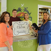 Town Clerk Debbie Aurelia, left, congratulates Anne Hoffmann, right, who stands with Chloe the cocker spaniel, Newtown's Number One Dog this year. Behind the counter is Mary Kay Novak, owner of Your Healthy Pet, and her son Ryan, who presented Chloe with a gift certificate on July 13.  (Bobowick photo)