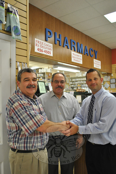 Drug Center Pharmacy owner and pharmacist Don Bates, left, shakes hands with Jonah Tyler, pharmacy supervisor for Walgreens, Tuesday, August 2, while Walgreens pharmacy manager Vincent Addorisio looks on. As of Friday morning, August 5, the Drug Center Pharmacy prescriptions and prescription client files will be transferred to Walgreens Pharmacy, located at the corner of Route 25 and Wasserman Way.  (Crevier photo)