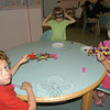 From left, Shawn Kuehling, Maggie Kuehling, and Grace Kuehling work on Mardi Gras masks in C.H. Booth Library's Story Time room on Monday, August 1, during the Crafts Around the World program.  (Hallabeck photo)