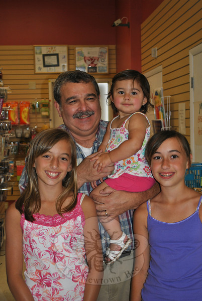 Retiring from the pharmacy business means more time to spend with his three granddaugh-ters, says Drug Center pharmacist and owner Don Bates, holding 18-month old Gabriella Brunelli. Standing with their grandfather are 11-year-old twins Mia, left, and Bianca Brunelli.  (Crevier photo)