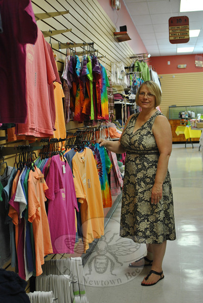 Diane Bates looks over a line of T-shirts and sweatshirts at the Drug Center on Church Hill Road. Ms Bates and her daughter, TeriAnn Brunelli, will open Everything Newtown in the former Drug Center Pharmacy on Friday, August 5, expanding the Newtown-focused gift lines and other gift items currently carried by the local drug store.  (Crevier photo)