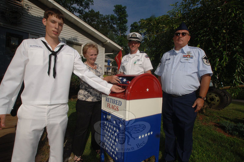 "Boy Scout Robert ""Bobby"" Mascher, left, holds open the hatch on the new permanent drop box for retired flags. First Selectman Pat Llodra places a folded flag inside. Bobby completed the retired flag box as his Eagle Scout project, which he presented to the Veterans of Foreign Wars Post 308 on Freedom Defenders Way, which is at the end of Tinkerfield Road. With him is Sea Scout leader Chip Rieve, and VFW Vice Commander James Rebman, far right.  (Bobowick photo)"