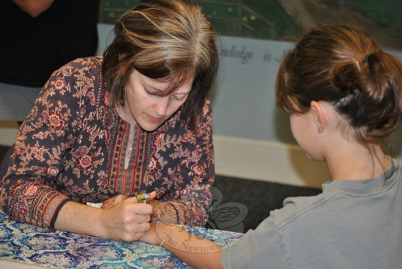 Eight-year-old Grace O'Connell holds her hand still as henna artist Genevieve Levin of ReMarkable Blackbird applies a design during a special program at the C.H. Booth Library, Wednesday, August 3.  (Crevier photo)