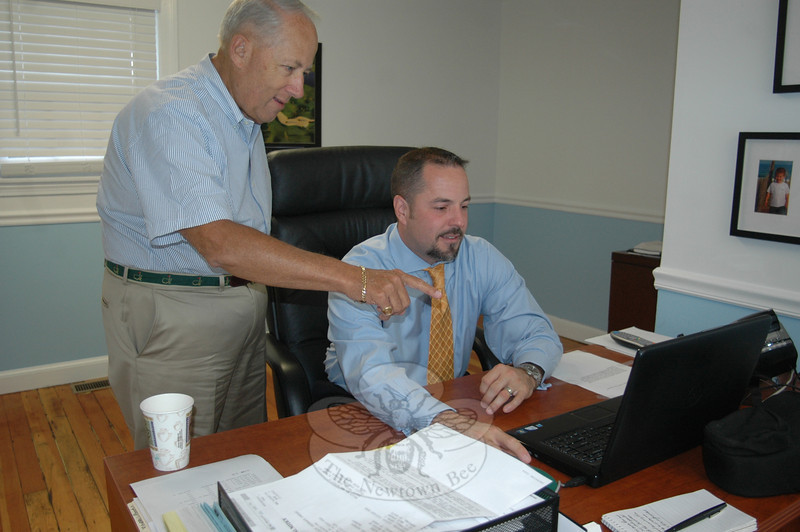 Longtime local Allstate agency owner Michael Snyder looks over some data with new owner Peter Stockwell. Mr Stockwell and his wife Jennifer recently acquired the local Allstate agency and are ramping up the already diverse number of insurance and financial services being made available to clients, Newtown residents and businesses.  (Voket photo)
