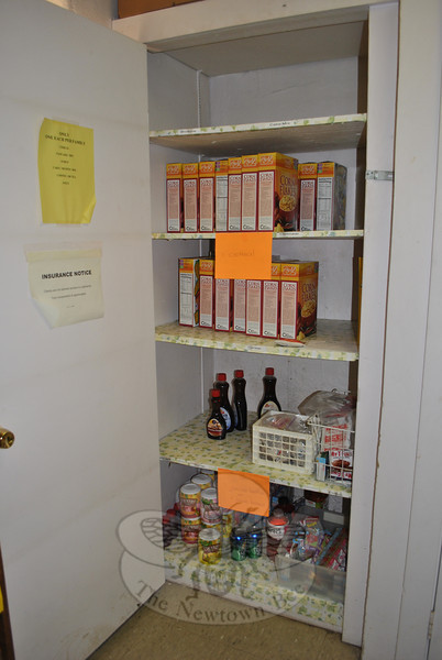 A few bottles of pancake syrup, some lemonade mix, and numerous boxes of cornflakes are all that shoppers have to select from in this cupboard at FAITH Food Pantry, currently. Donations of other cereals, stews, baked beans, and complete pancake mix are desperately needed, along with other nonperishable foods and toiletries, says FAITH coordinator Lee Paulsen.  (Crevier photo)