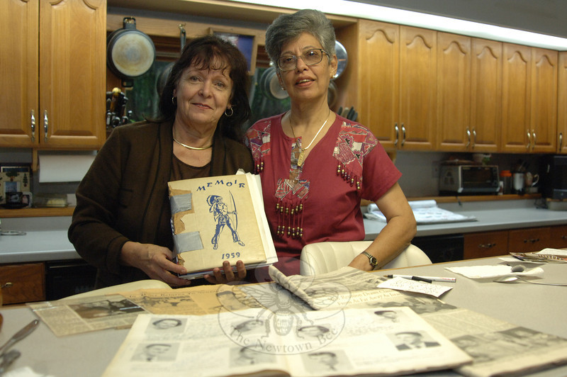 Newtown High School Class of 1959 graduates June Hanna, left, and Zarin Patel, the first American Field Service student to visit town, look at old yearbook photos during Ms Patel's recent visit in late June. A Pakistani native, Ms Patel first visited Newtown in 1959, and has stayed in touch with Ms Hanna ever since. She has made several trips to the United States, and remains friends with several long-ago Newtown classmates.  (Bobowick photo)