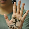 Juliana Patelli shows off the tree of life design she had painted on her palm at the Henna Body Art program at the library, Wednesday, August 3.  (Crevier photo)