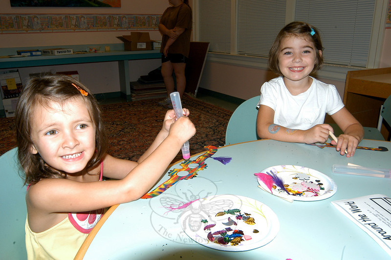 Ellie Boni, left, and Caroline Previdi created Mardi Gras masks during the library's Crafts Around the World program on Monday, August 1.   (Hallabeck photo)
