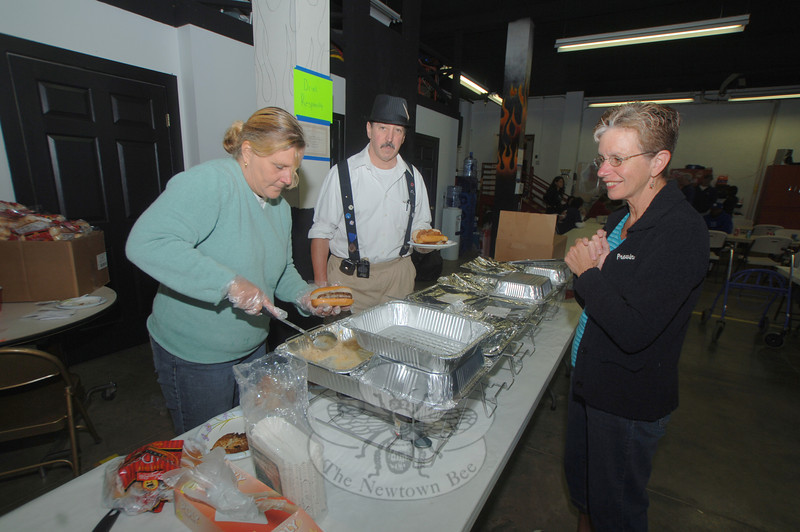 Karen Dugan and 32-year department member Marty Schertzer prepare a dinner plate for guest Susan Doyle.  (Bobowick photo)