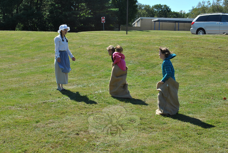 Emma Walsh, 8, center, races Genny Kelly, 8, to the finish line where docent Maren Brady, 13, waits. Sack races were among several games played by children at the open house sponsored by Newtown Historical Society, Sunday, September 18, at the old Middle Gate School-house on Cold Spring Road.  (Crevier photo)