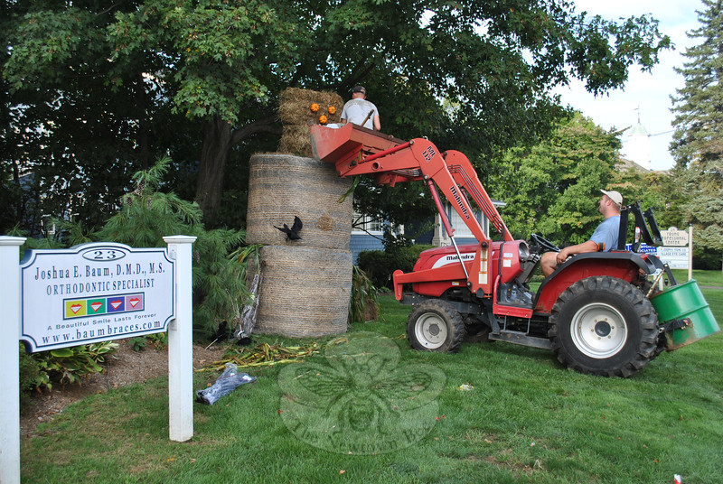 "The arrival of the annual ""Hay Lady"" in front of the office of Dr Joshua Baum, at 23 Church Hill Road, was delayed by Tropical Storm Irene and the following torrential rains, but on Tuesday afternoon, September 27, Bill Henckel of W.T. Henckel Lawn and Landscape, LLC, gave Bill Pendergast of Pendergast Lawn Care, LLC, a lift in the bucket of the tractor to construct the towering figure. Here, Mr Pendergast attaches pumpkin eyes and a pumpkin nose to the hay bale face. Cornstalks lay to the side, ready to be turned into a skirt, attached to the lower of the two round bales making up the body of the Hay Lady.  (Crevier photo)"