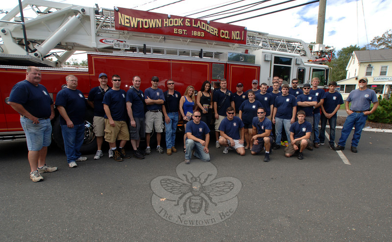 Newtown Hook & Ladder Fire Co. #1 members, officers, and supporters gather in front of the company's ladder truck Sunday.  (Bobowick photo)