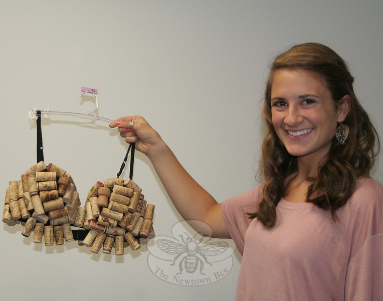 "Newtown High School student Nicole DeFelice created ""Stop Whining: Get Yourself Tested"" using a collection of wine bottle corks. She is one of six NHS students who have shared their talents to create artfully decorated brassieres for this weekend's ""2x2: Artful Bras & Boxers"" events. A formal cabaret evening will be hosted by Newtown United LLC on Saturday in Edmond Town Hall's Alexandria Room, and a fall marketplace will then run on Sunday afternoon in the same location.  (Hicks photo)"