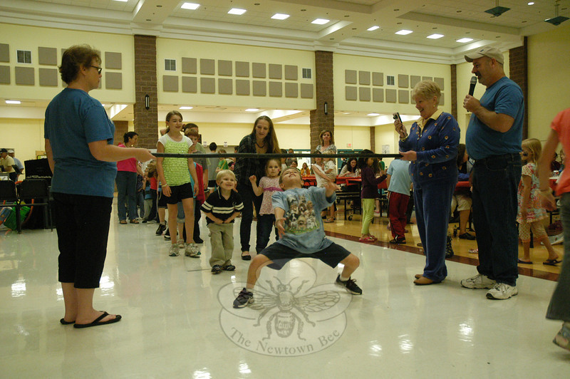 A group of youths at the Family Dinner/Fun Night held on Friday, September 23, performed the limbo dance in the cafetorium at Reed Intermediate School at Trades Lane. The dancers bent and stretched into various postures to get beneath the limbo pole as it was progressively lowered during successive passes.  (Gorosko photo)