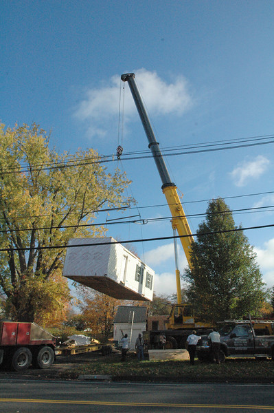 On Tuesday, October 26, workers using a hydraulic crane hoisted sections of a new modular house into place at 5 South Main Street, across the street from The Ram Pasture. The four modular sections erected by Westchester Modular Homes of Fairfield County, Inc, will comprise a new Colonial-style house that should be completed by mid-December, when interior outfitting is finished. The new approximately 1,500-square-foot house to be occupied by the Wheeler-Taylor family replaces a former Cape Cod-style house on the site that was heavily damaged in May 2009 when an almost 100-foot-tall silver maple tree fell onto that structure during high winds.  (Gorosko photo)