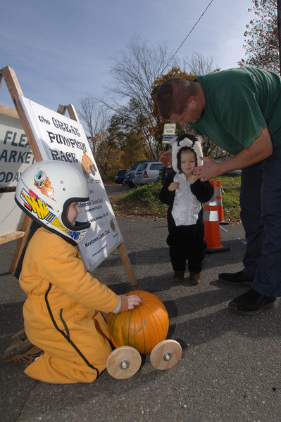 Connor Sinapi is bundled in the same mustard-colored body suit and helmet that his father Greg had worn as a child. As Connor prepares to race his pumpkin down the slope, his father talks with sister Kayla.  (Bobowick photo)