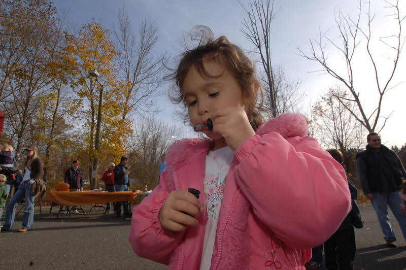 With the mini wand near her lips, Olivia Sims stood still to blow bubbles that the wind caught and carried.  (Bobowick photo)