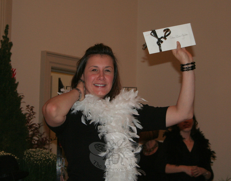 Lori Zezza during the live auction, with a gift certificate for Stone River Grille.  (Hicks photo)