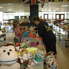 Newtown High School Marching Band and Guard tag sale volunteer Dot Perpignand, right, helps 7-year-old Courtney find a new cuddly friend. She seemed quite drawn to the smiling monkey in the foreground, and ended up taking it home. (Voket photo)